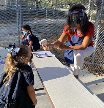 St. Bonaventure's Alicia Dominguez checks a PreK4 student's temperature on the first day of the 2020-2021 school year, Aug. 19, 2020. PreK students