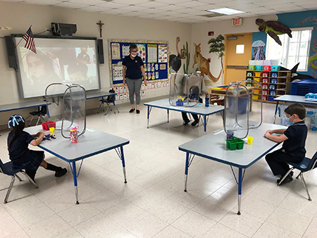 Photo of a socially distanced PreK4 classroom at Mother of Our Redeemer School, Miami, on the first day of school, Aug. 19, 2020. The in-person students are surrounded by sneeze guards at their desks, the teacher, Patricia Medina, is wearing a mask/shield, and other students are learning from home.