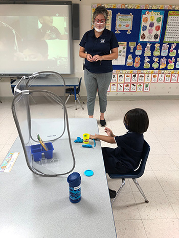 Photo of a socially distanced PreK4 classroom at Mother of Our Redeemer School, Miami, on the first day of school, Aug. 19, 2020. The in-person students are surrounded by sneeze guards at their desks, teacher Patricia Medina is wearing a mask/shield and other students are learning from home.