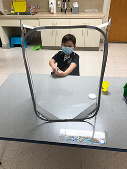 Alex Rodriguez, a PreK4 student at Mother of Our Redeemer School, Miami, is surrounded by a sneeze guard and wearing a mask on the first day of school, Aug. 19, 2020.