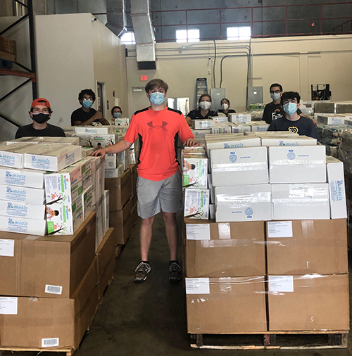 Belen Jesuit students are shown here volunteering at a warehouse in Doral, where they helped sort donations of baby goods to benefit parishes and local pregnancy help centers associated with the archdiocese's Respect Life Ministry.
