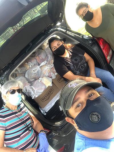"""Con máscaras faciales y un baúl lleno de comida, el equipo del Centro Educativo La Salle - Silvia Muñoz, Mónica Lauzurique, Dulce Olivera y Yancy Velásquez -se hacen un """"selfie"""" antes de distribuir las donaciones de alimentos puerta a puerta en el Campamento de Trabajadores Agrícolas de South Dade, donde 300 unidades albergan a adultos, familias con niños y ancianos."""