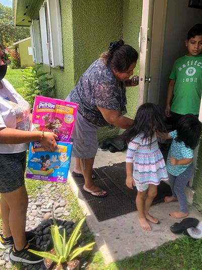 Voluntarios del Centro Educativo La Salle entregan pañales a las familias con niños pequeños que viven en Campamento de Trabajadores Agrícolas de South Dade. Muchos de los pañales fueron donados por la escuela jesuita de Belén.