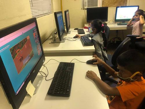 Con máscaras faciales, los niños del Centro Educativo La Salle utilizan las computadoras para aprender y jugar durante el campamento de verano 2020.