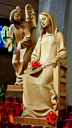 Gabriel announces the future birth of Jesus to a pensive Mary. Someone has placed a flower on her lap.