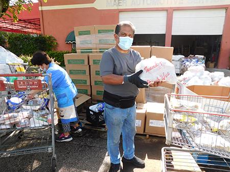 César Coronado, ministro laico de la iglesia Mother of Christ, en Miami y Nancy Bohnenblust, una entusiasta voluntaria, colocan las bolsas de alimentos en los autos que avanzan en una larga fila.