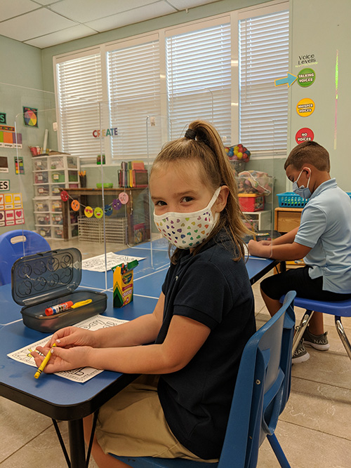 Abigail Kyer, in Kindergarten, settles into her new desk on the first day of the 2020 academic year at The Basilica School of St. Mary Star of the Sea, wearing her colorful face mask.