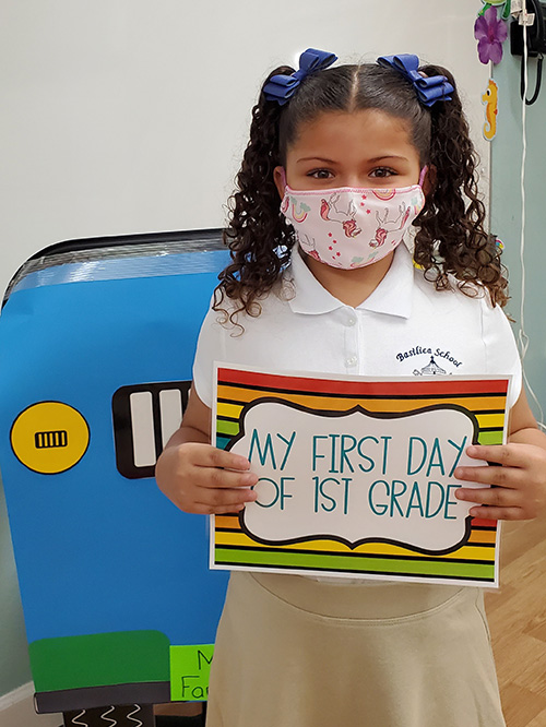 Mila Cabrera, dressed in uniform and with her hair decorated in ribbons, holds up a sign and poses for a photo on her first day back to classes at The Basilica School of St. Mary Star of the Sea in Key West.