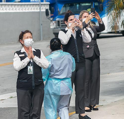 Devotos de la Virgen de la Caridad, en este caso empleados de Leon Medical Center, la saludan y toman fotos durante el recorrido de la Ermita hasta la iglesia St. Michael en Miami.