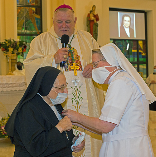 Salesian Sister Suzanne Dauwalter, right, pins the Primum Regnum Dei medal - the highest honor bestowed by the archdiocese - on fellow Salesian Sister Yamile Saieh as Archbishop Thomas Wenski looks on at the conclusion of her farewell Mass, celebrated at Notre Dame d'Haiti Church in Miami, Sept. 15, 2020.