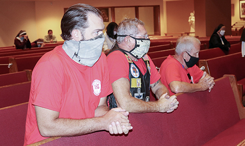 Knights on Bikes Tony Orband, Lance Maki and Dale Saunders pray while celebrating Mass with Archbishop Thomas Wenski Sept. 17, 2020, during a stop at the archdiocesan Pastoral Center in Miami Shores. They were riding to northern Florida along U.S. 1 to raise awareness about the rights enshrined in the First Amendment to the U.S. Constitution, notably freedom of religion and speech.