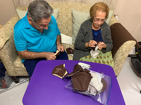 Members of the Secular Franciscan Order Espejo de Cristo (Mirror of Christ), Reny Aguilera, OFS, and Hilda Nieves help to turn the masks over after being sewn.