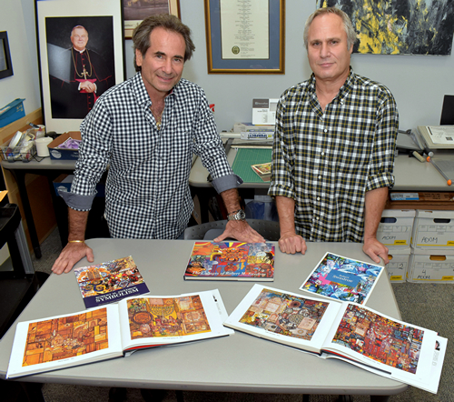 Marc Swedroe, left, and Freddy Sall show books of artwork by artist Robert Swedroe.