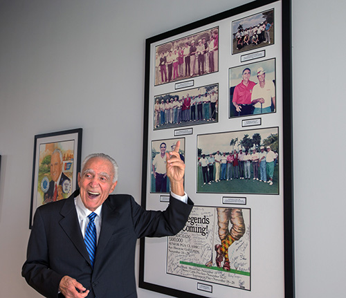 Gus Machado gestures to photos hanging on a wall in the new building from the Gus Machado Senior PGA classics he sponsored in the late 1980s. He has now given his name to the School of Business complex at St. Thomas University, dedicated Oct. 16, 2020.