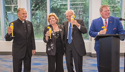 Msgr. Franklyn Casale, St. Thomas University's president emeritus, joins Lilliam Machado, her husband, Gus Machado, and David Armstrong, STU's current president, in a toast for the businessman and philanthropist after whom the College of Business complex is named.