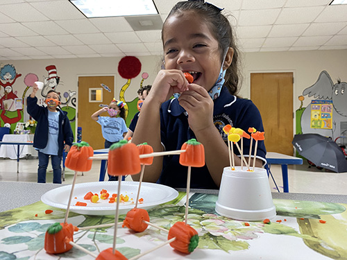 Mother of Our Redeemer PreK-3 student, Nicole Ayala, can't resist tasting some of her work on the Candy Corn Challenge.