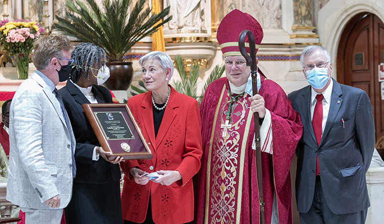 Senior Judge Patricia Seitz, standing next to Archbishop Thomas Wenski, presented the Miami Catholic Lawyers Guild's highest honor, the Lex Christi, Lex Amoris award, to Randy McGrorty, far left, and Myriam Mezadieu, executive director and COO, respectively, of Catholic Legal Services. The presentation took place at the conclusion of the annual Red Mass organized by the Miami Catholic Lawyers Guild, whose president, Francis Sexton, is pictured at far right. The Mass was celebrated Oct. 29, 2020.