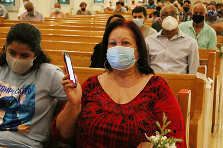 Virginia Salas, a Corpus Christi parishioner for over 30 years, takes out her smartphone to download the Corpus Radio app with the help of her granddaughter, Samanta Reyes, on October 4, during the launching Mass of the new community radio station.