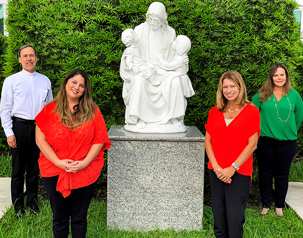 Posing near a statue of Jesus and the children on the campus of St. Thomas the Apostle School in Miami, from left:  Father Alejandro Rodriguez Artola, pastor; special education teacher Nichole Aranguren Garcia; principal Lisa Figueredo; and vice principal Angie Ayan-Novo. St. Thomas was named a 2020 Blue Ribbon School of Excellence by the U.S. Department of Education.