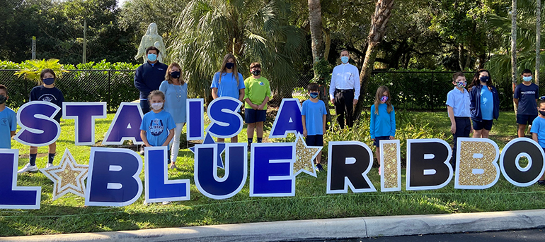 Students, principal Lisa Figueredo (middle left) and pastor, Father Alejandro Rodriguez Artola (rear right)pose amid the Blue Ribbon sign on the lawn of St. Thomas the Apostle School in Miami, which was one of two archdiocesan schools honored by the U.S. Department of Education in 2020.