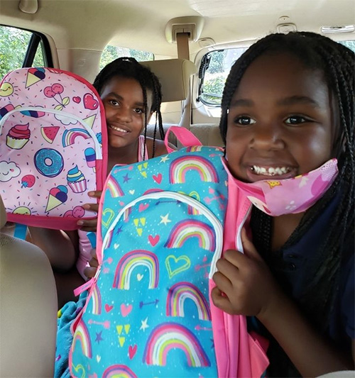 Two of the 175 recipients show off the backpacks they got at Hope, Heart & Home ministry's Aug. 8, 2020 giveaway at St. John Neumann Church in Miami.