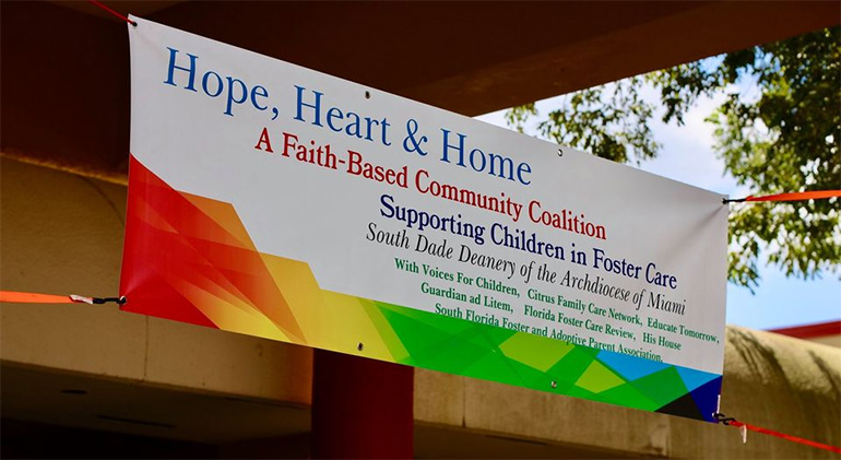Hope, Heart & Home ministry's banner hangs at the entrance to St. John Neumann Church in Miami during the backpack giveaway in August.