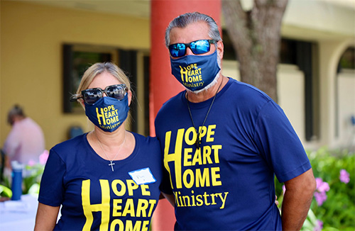 Lorenzo Cosio, Jr., and his wife, Pam, pose for a photo during the backpack giveaway at St. John Neumann Church in August 2020. He is the Hope, Heart & Home ministry's marketing director and liaison to St. Louis Church in Pinecrest.