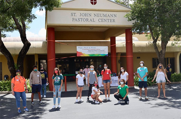 Young adult volunteers are ready to help Hope, Heart & Home load backpacks into cars at the ministry's August giveaway at St. John Neumann Parish in Miami.