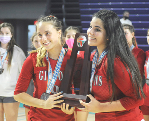 Cardinal Gibbons senior captains Manuela Williamson, left, and Valeria Lozada pose with the runner-up trophy after the FHSAA Class 4A volleyball state final match Nov. 15, 2020 at Suncoast Credit Union Arena in Fort Myers. Bishop Kenny defeated Cardinal Gibbons 29-27, 25-18, 17-25, 25-20 to win their third state title.