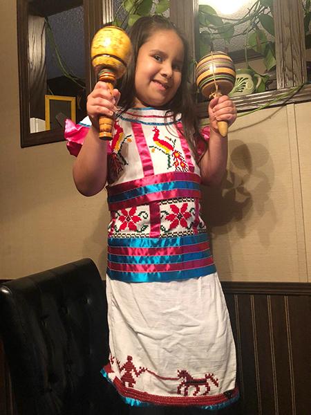 La niña Catalina Uribe, vestida con su traje tradicional de Guatemala, desde Misisipi, participó en el campamento virtual con niños de la escuela St. Hugh, en Miami.