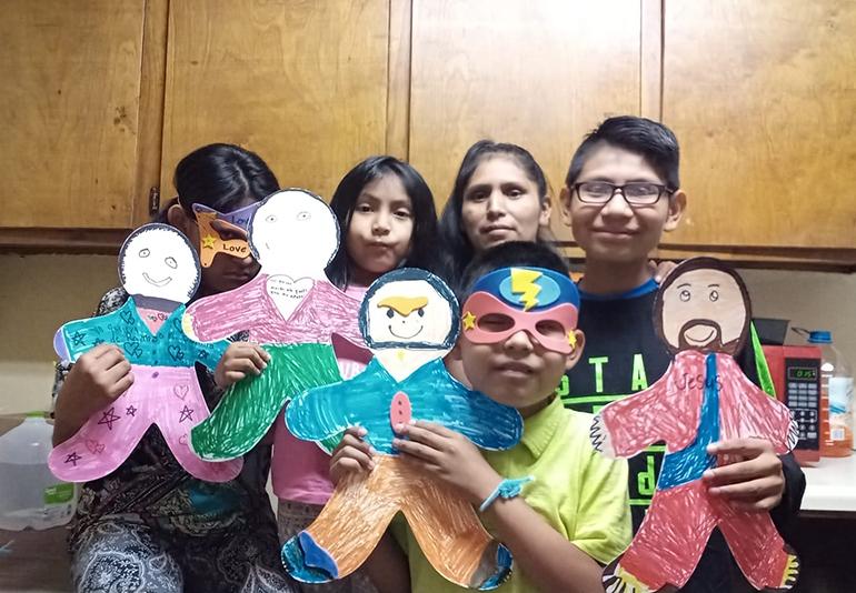 La señora Isabel Ramos con sus tres hijos y un sobrino, desde Misisipi, participan en una actividad del campamento virtual con niños de la escuela St. Hugh, en Miami.
