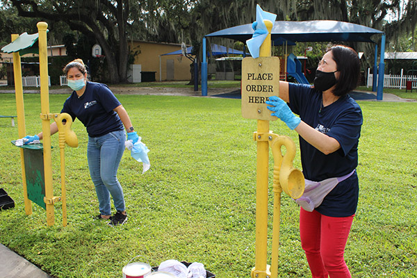 Before painting, Solanghe Rodriguez and Adriana Kambe wipe down playground equipment at Catholic Charities of the Archdiocese of Miami's Notre Dame Child Development Center in Little Haiti, Nov. 5, 2020. The two, who work with the accounting and advising firm Hancock, Askew and Co., volunteered for a service day.