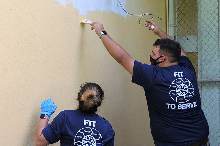 Just a little higher: Anthony Perez-Florido helps Solanghe Rodriguez paint a spot out of her reach. The two, who work with Hancock, Askew and Co., volunteered with others from their accounting firm to beautify Catholic Charities of the Archdiocese of Miami's Notre Dame Child Development Center in Little Haiti, Nov. 5, 2020. The accountants and auditors at Hancock, Askew and Co. participate twice a year in community service projects across the state.