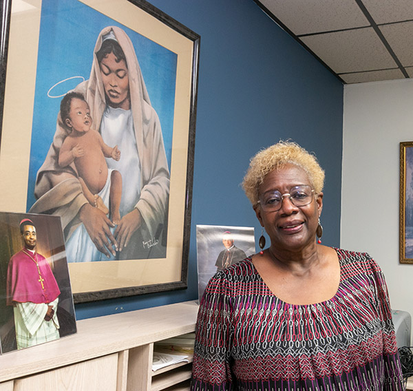 Katrenia Reeves-Jackman, director of the archdiocesan Office of Black Catholic Ministry, poses in front of a painting of a black Madonna and child. The picture at left is of a very young bishop, now Cardinal-elect Wilton Gregory of Washington, D.C., the first African-American to be elevated to that rank.