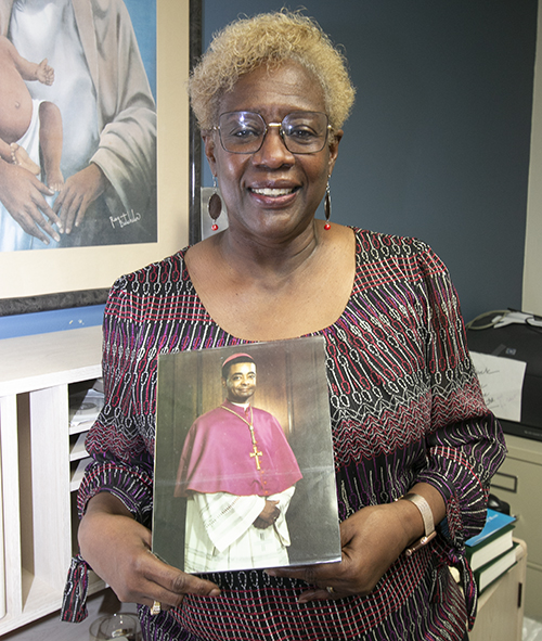 Katrenia Reeves-Jackman, director of the archdiocesan Office of Black Catholic Ministry, holds up a picture of a very young bishop, now Cardinal-elect Wilton Gregory of Washington, D.C., the first African-American to be elevated to that rank.