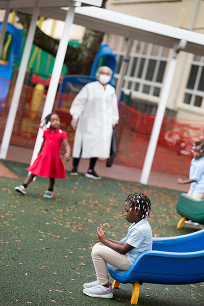 Staff clad in personal protective equipment look on as youngsters enjoy recess at the Catholic Charities-sponsored child development center/Head Start program at Holy Redeemer Church in Miami. It is one of six such programs throughout Miami-Dade County operating at reduced in-class capacity during the COVID-19 global pandemic.