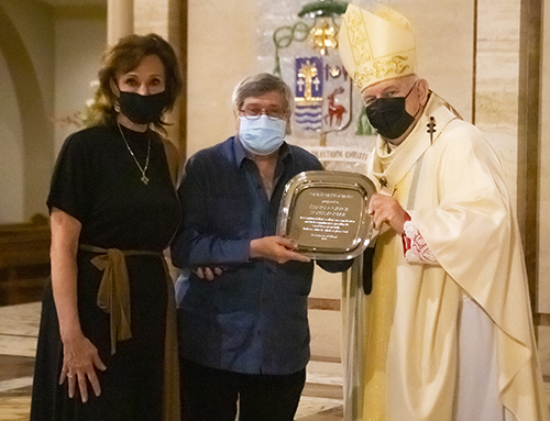 Archbishop Thomas Wenski gives Henry and Grace Lopez-Aguiar the One in Faith award during the Thanks-for-Giving Mass celebrated at St. Mary Cathedral, Nov. 21, 2020.