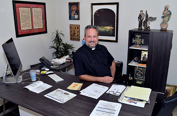 Father David Zirilli shows his new desk, which allows him to sit or stand. The desk is housed in a complex of offices, rectory and a chapel, dedicated this past May 2020.