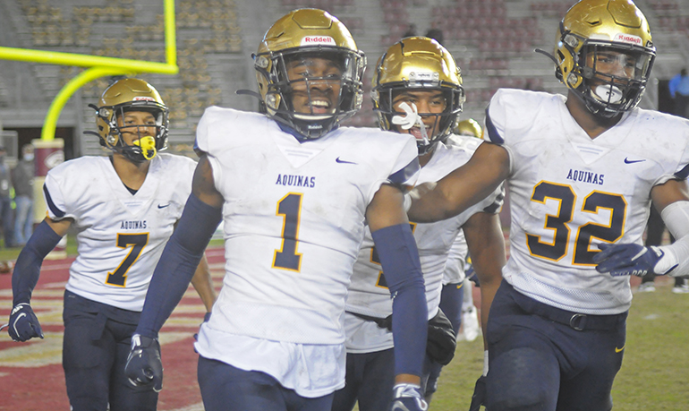 Ja'Den McBurrows (1) joins teammates Tyson Russell (7) and Jaydon Hood (32) in celebrating McBurrows' 46-yard interception return for a touchdown late during the first half of St. Thomas Aquinas' 31-21 victory over Orlando Edgewater, Dec. 19, 2020, in the FHSAA Class 7A Football State Championship Game at Bobby Bowden Field at Doak Campbell Stadium. The Raiders won their state-record 12th title.