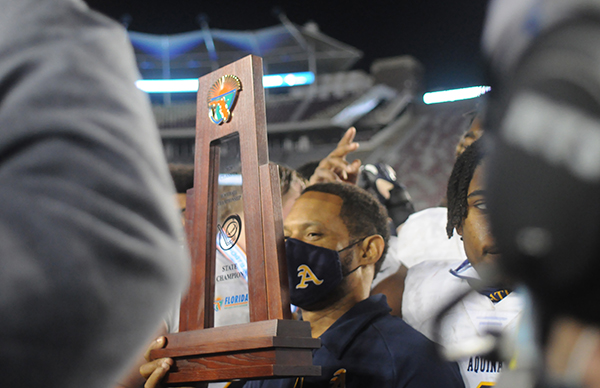 St. Thomas Aquinas coach Roger Harriott holds onto the trophy while celebrating the Raiders' 31-21 victory over Orlando Edgewater, Dec. 19, 2020, in the FHSAA Class 7A Football State Championship Game at Bobby Bowden Field at Doak Campbell Stadium. The Raiders won their state-record 12th title.