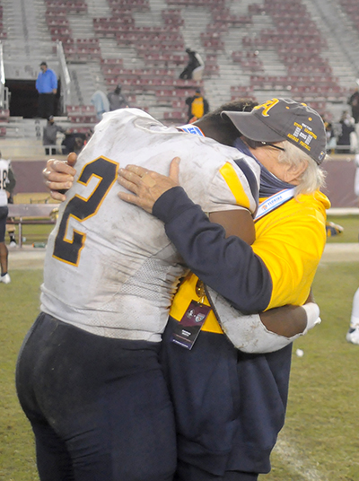 Athletic director George Smith hugs senior captain Tyreak Sapp as other players celebrate St. Thomas Aquinas' 31-21 victory over Orlando Edgewater, Dec. 19, 2020, in the FHSAA Class 7A Football State Championship Game at Bobby Bowden Field at Doak Campbell Stadium. The Raiders won their state-record 12th title.