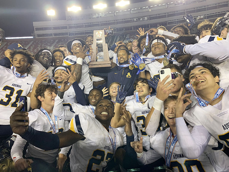 Coach Roger Harriott joins his players with the trophy in celebrating St. Thomas Aquinas' 31-21 victory over Orlando Edgewater, Dec. 19, 2020, in the FHSAA Class 7A Football State Championship Game at Bobby Bowden Field at Doak Campbell Stadium. The Raiders won their state-record 12th title.