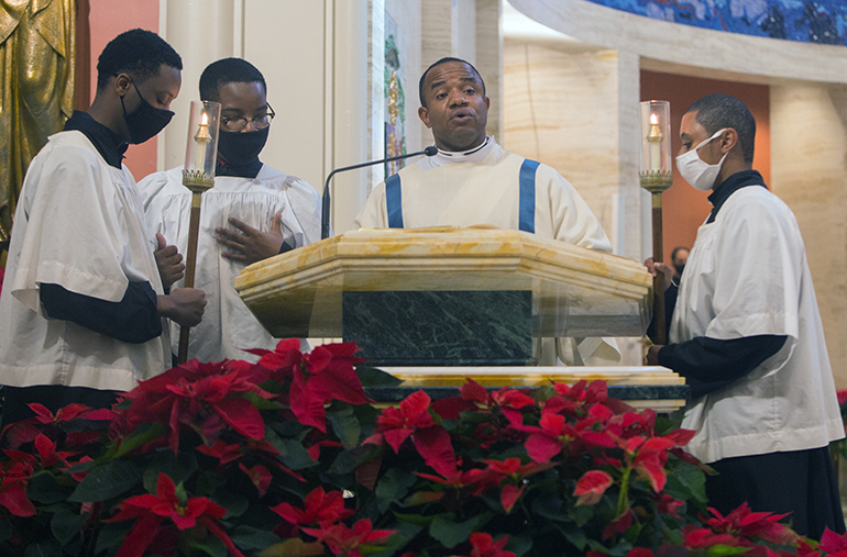 Transitiional Deacon Franklyn Ekezie, a native of Nigeria, proclaims the Gospel in his native tongue, Igbo, during the annual Migration Mass, celebrated by Archbishop Thomas Wenski at St. Mary Cathedral on the feast of the Epiphany, Jan. 3, 2021.
