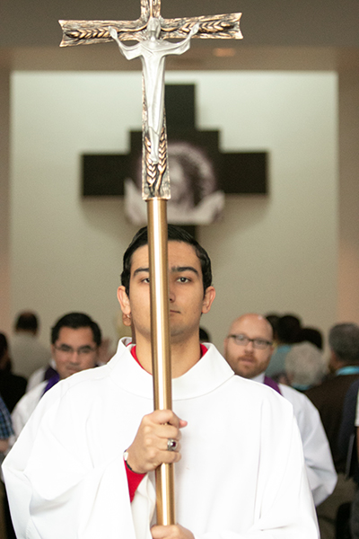 "A Msgr. Edward Pace High student holds the processional cross during a Mass at the school in this file photo from 2019.  Pope Paul VI abolished the minor orders (and the subdiaconate) and established the ministries of lector and acolyte in the motu proprio, ""Ministeria quaedam,"" issued in 1972. Now Pope Francis has opened both ministries to women."