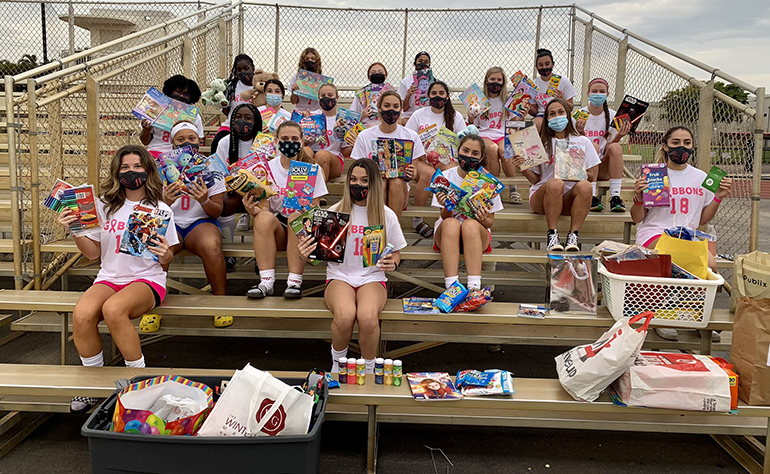 Cardinal Gibbons girls' soccer players pose with some of the donations collected at the Coaches vs. Cancer game held Jan. 13, 2021 on the Gibbons field.