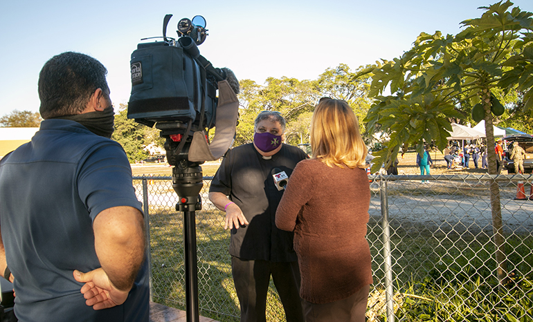Father Jose Espino, pastor of San Lazaro Parish in Hialeah, speaks with a reporter from Telemundo 51 as the vaccinations get underway behind him, Jan. 20, 2021.