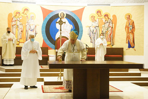 Archbishop Thomas Wenski pours oil of chrism on the new altar at Mother of Christ Church in Miami, Jan. 1, 2021. He also blessed the refurbished worship space. Behind him is a painting of Christ Pantocrator which will also be getting a touch-up soon.