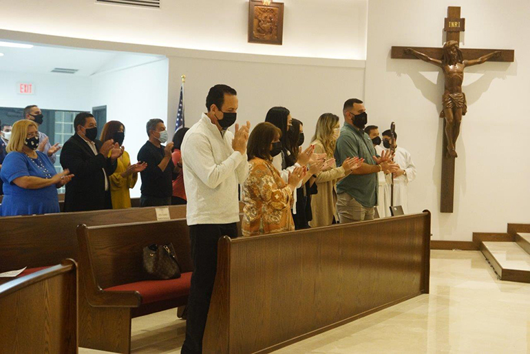 Parishioners applaud during the Mass where Archbishop Thomas Wenski consecrated the new altar at Mother of Christ Church in Miami, Jan. 1, 2021. He also blessed the refurbished worship space. Visible at rear is the new life-size crucifix carved out of wood as well as one of the new wood-carved Stations of the Cross.