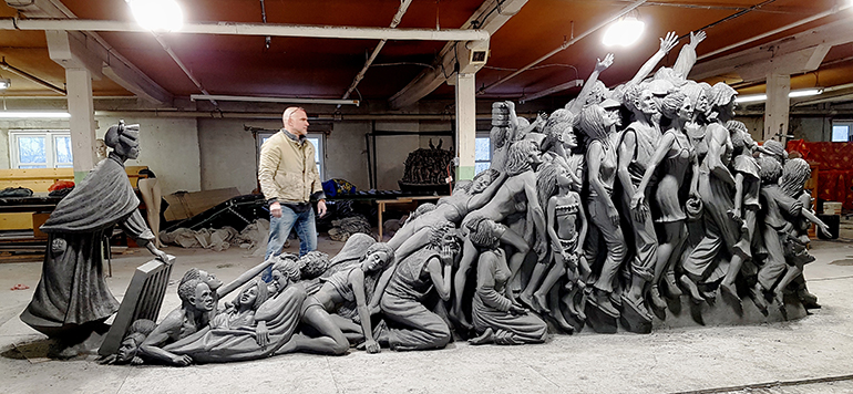 "Sculptor Timothy Schmalz looks over his next sculpture, ""Let the Oppressed Go Free."" The figure at left is St. Josephine Bakhita, patron saint of human trafficking."