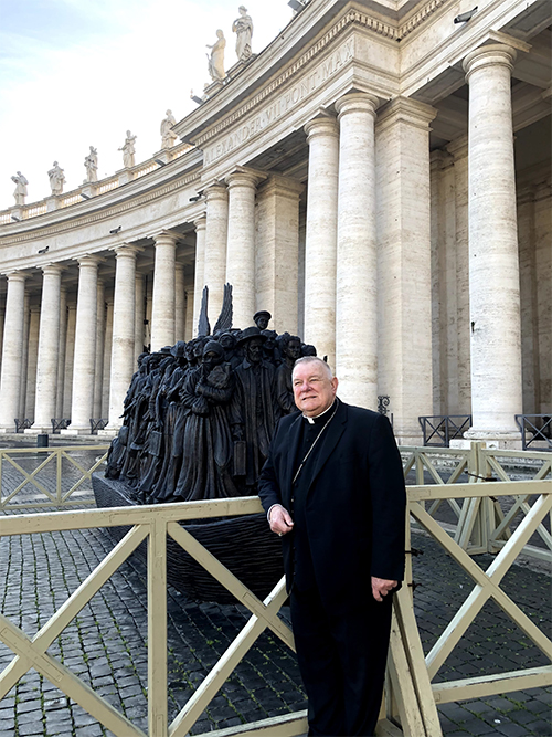 Archbishop Thomas Wenski poses in front of the Angels Unawares sculpture on display in St. Peter's Square during his February 2020 visit to Rome for his ad limina visit with Pope Francis. A replica will be on display at Miami's Bayfront Park from Feb. 9 to April 8, 2021.